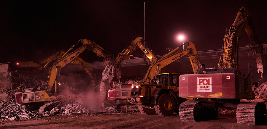 A line of machines dig into the bridge