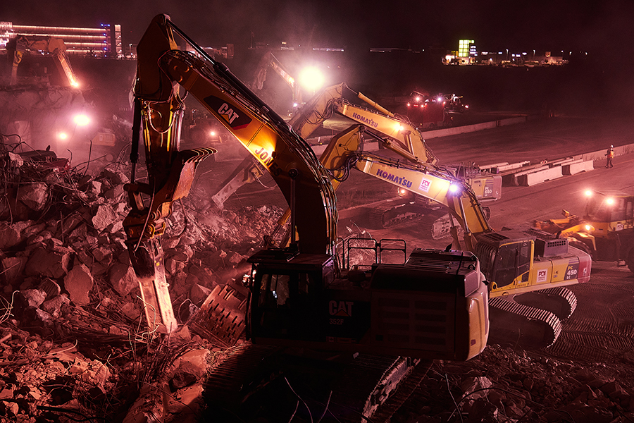 Machinery surveying the pile of rubble